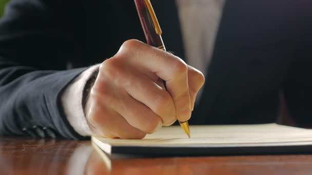 depositphotos_117841296-stock-video-closeup-of-business-man-writing